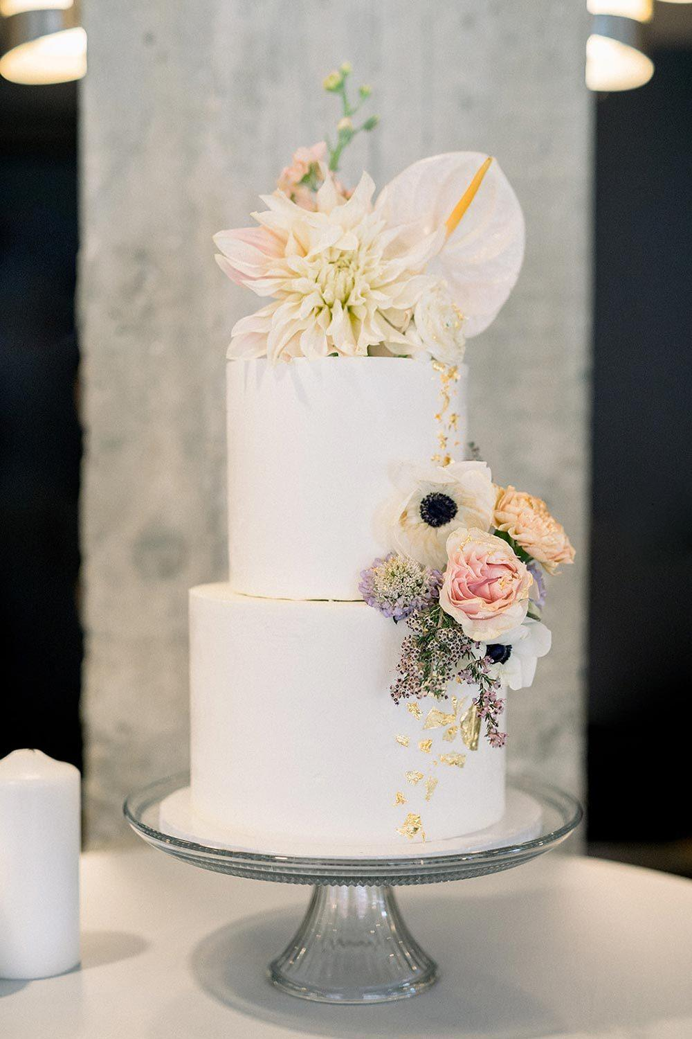 modern wedding cake with anemones, anthuriums and dahlias