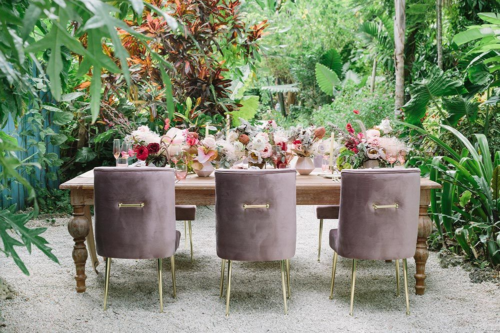 farmhouse wedding table with pink velvet chairs and silk flowers