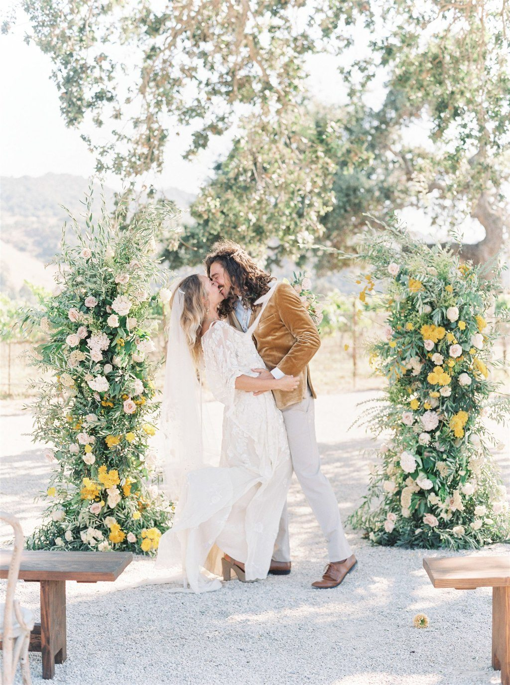 silk kaftan wedding dress and gold velvet groom suit with asymmetrical floral arches for a California vineyard wedding
