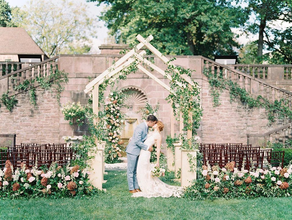 formal garden wedding with custom wooden aisle arch and greenery