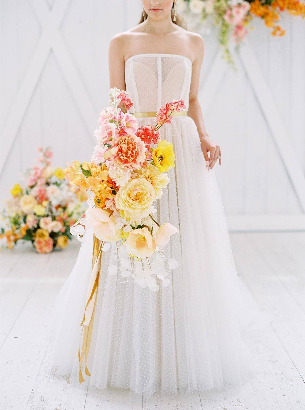 citrus bridal bouquet with modern strapless wedding dress with sequins and corset bodice
