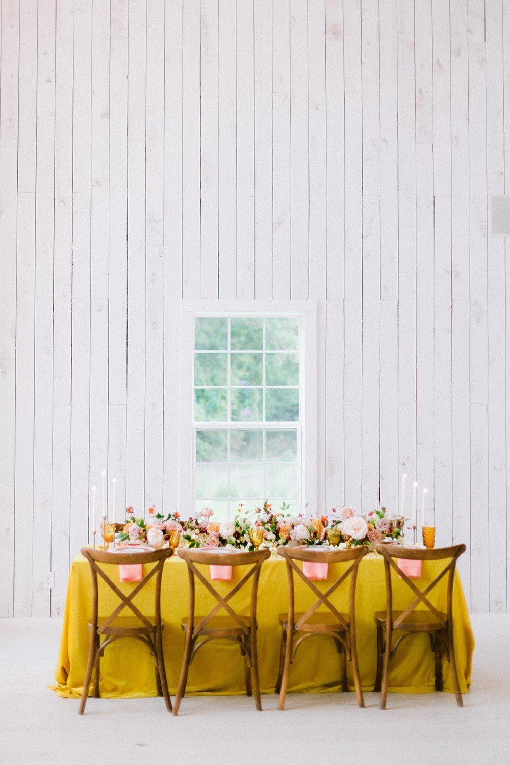 yellow wedding tablescape with cross back chairs and peach napkins