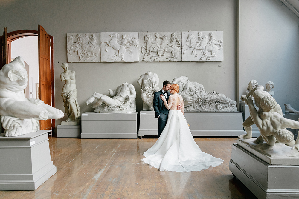 sweeping lace bridal gown with black suit for an art gallery wedding
