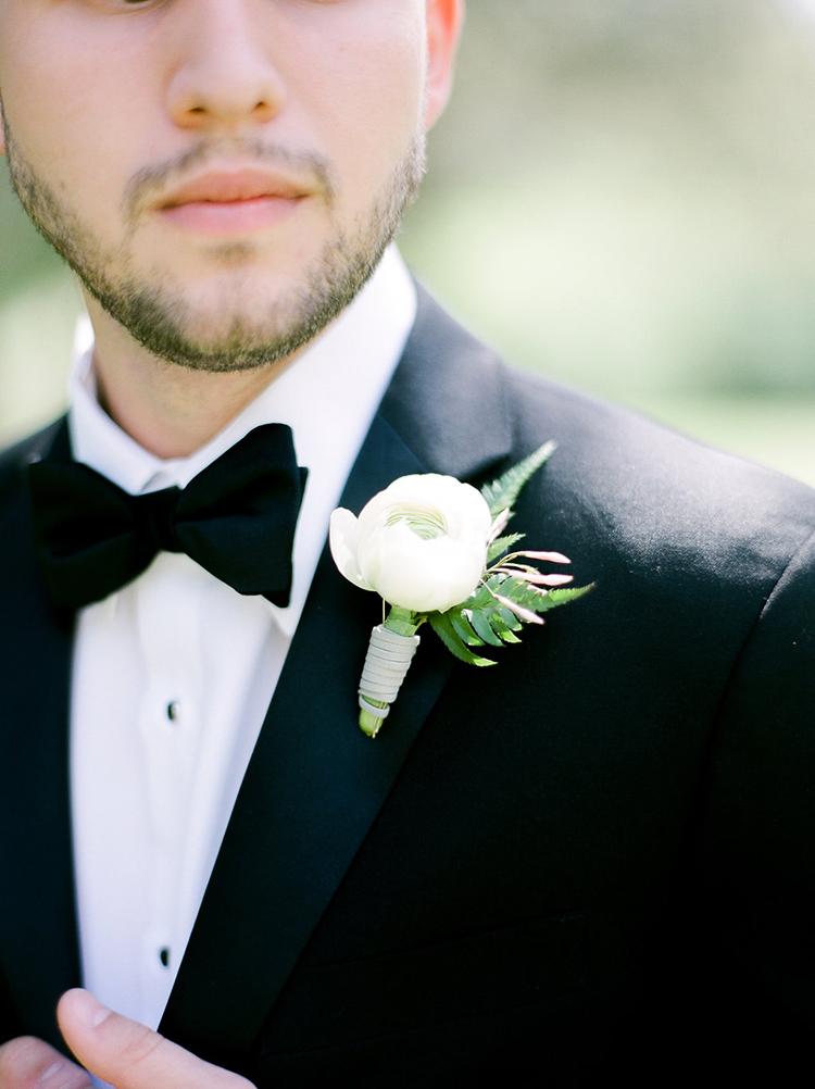 ivory ranunculus boutonnieres - photo by Christy Wilson Photography https://ruffledblog.com/summer-castle-soiree-wedding-inspiration