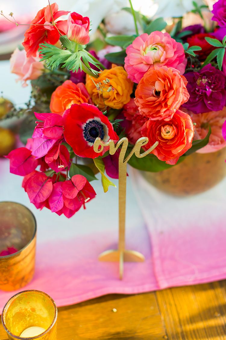gold table numbers - photo by Ana and Jerome http://ruffledblog.com/summer-destination-wedding-in-mexico-with-bright-pinks