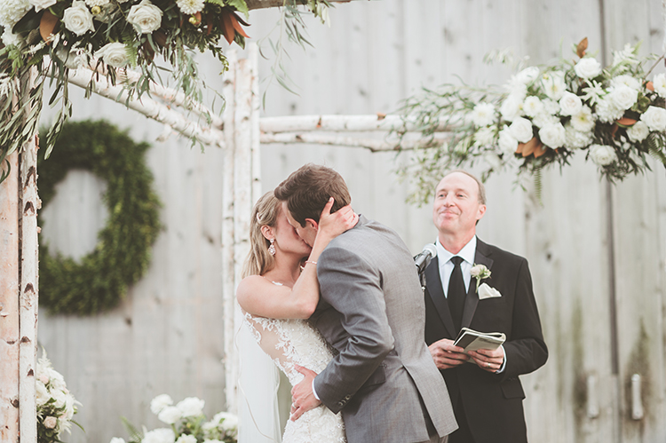 ceremony kiss - photo by Paper Antler https://ruffledblog.com/summer-sunset-wedding-in-wisconsin