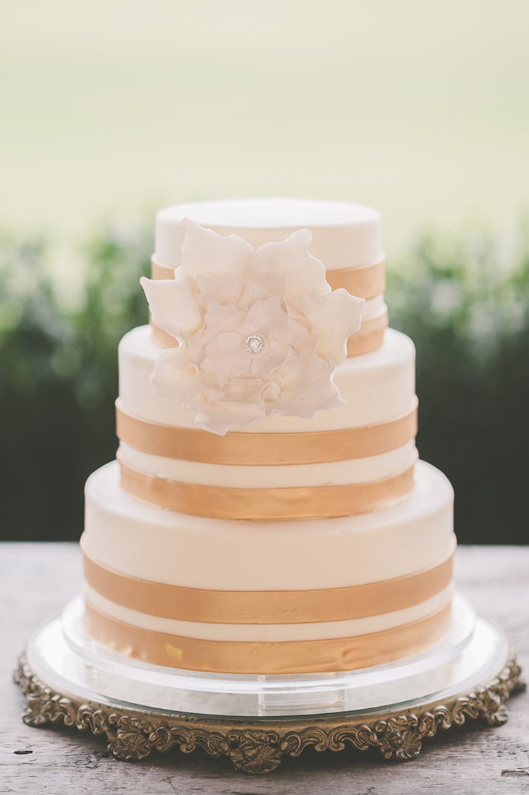 gold and ivory wedding cake - photo by Paper Antler https://ruffledblog.com/summer-sunset-wedding-in-wisconsin