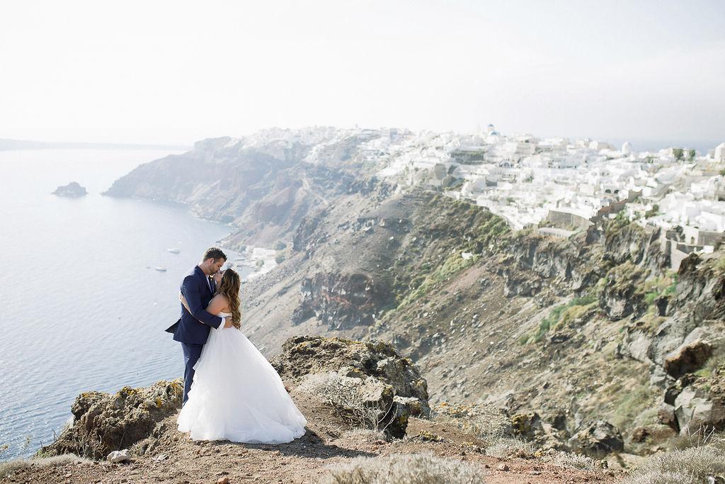 ruffled wedding dress and navy groom suit Santorini couple portraits