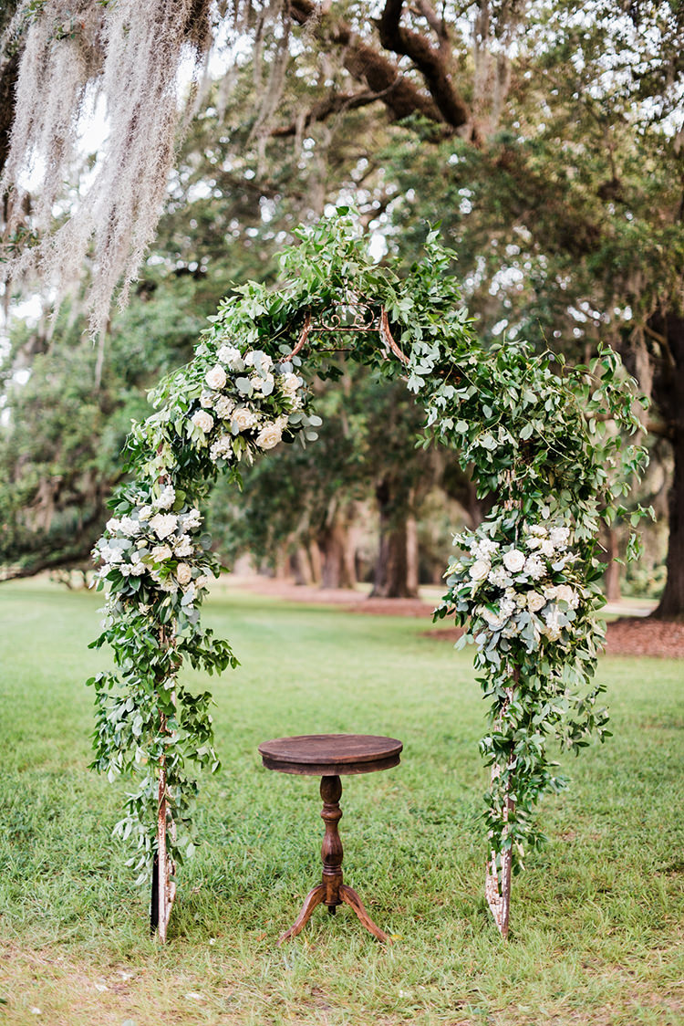 ceremony arches with greenery and flowers - https://ruffledblog.com/swoon-worthy-charleston-wedding-with-spanish-moss