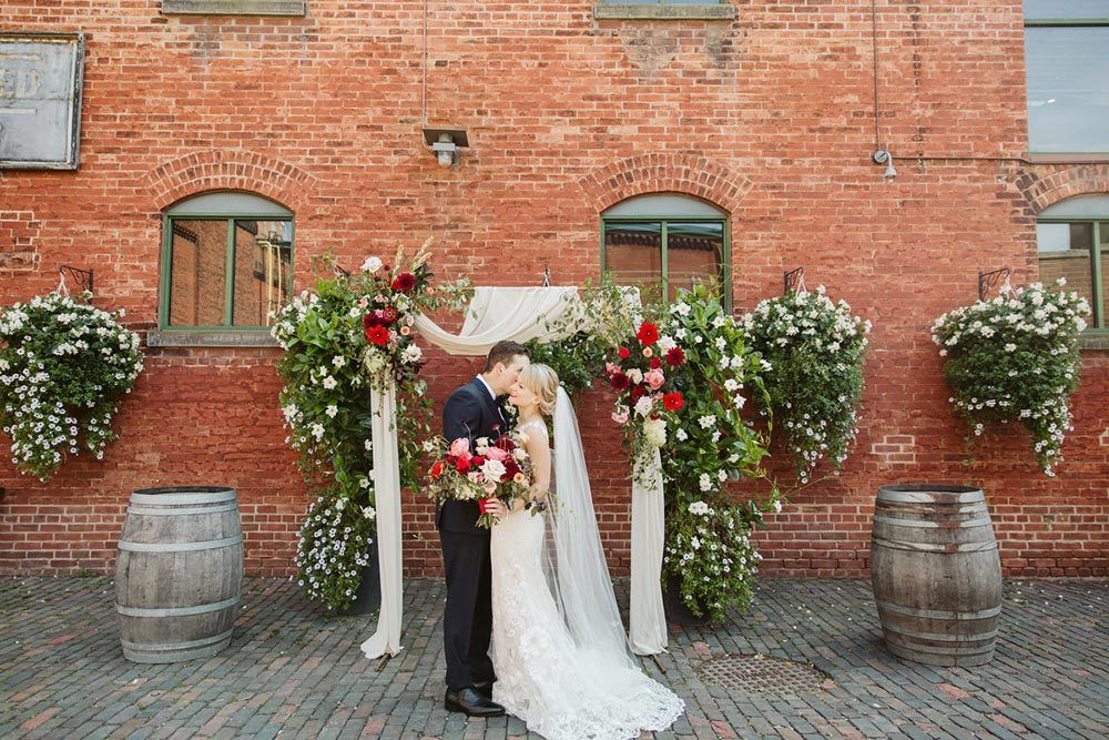 industrial chic wedding ceremony with burgundy flowers and romantic draping