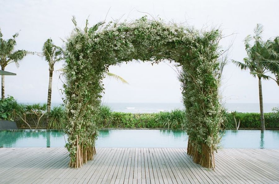 Bali wedding ceremony with tropical greenery arbor and pool view
