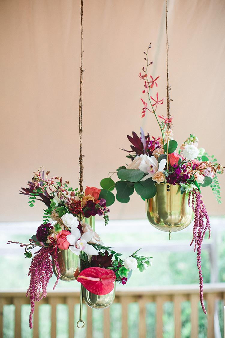 brass hanging planters - https://ruffledblog.com/tropical-glamping-wedding-inspiration-with-moody-hues