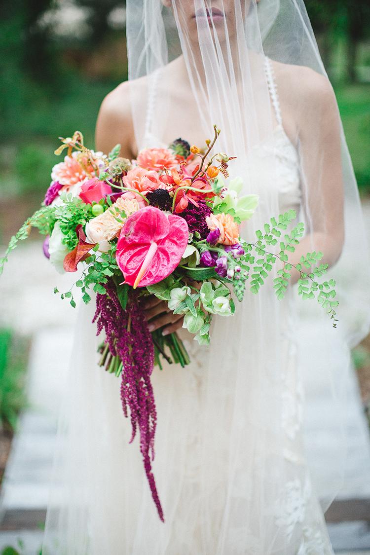 tropical pink wedding bouquets - https://ruffledblog.com/tropical-glamping-wedding-inspiration-with-moody-hues