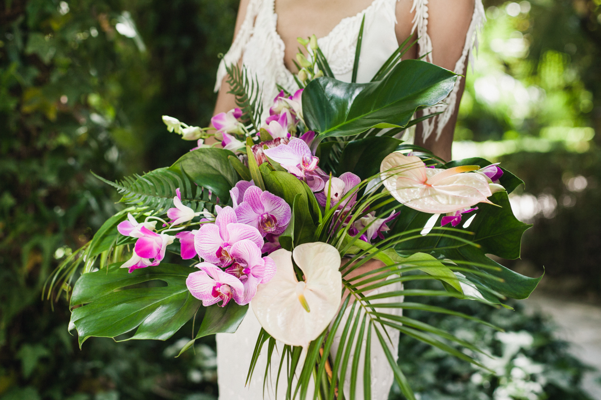 tropical wedding bouquets with orchids - photo by Sarah and Nora Photographers https://ruffledblog.com/tropical-spanish-wedding-inspiration-with-philodendrons
