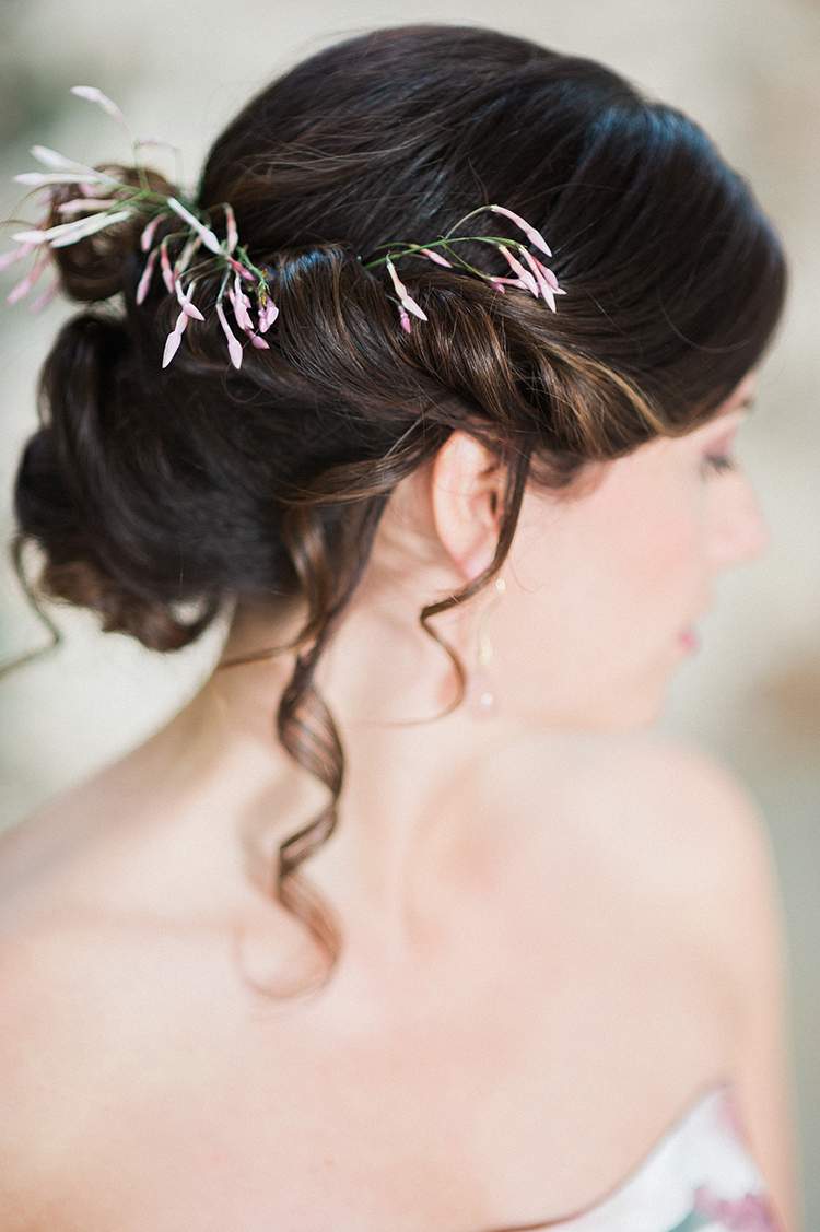 wedding updos with delicate flowers - photo by Linda Nari Photography https://ruffledblog.com/tuscan-warehouse-wedding-inspiration-with-a-floral-bridal-gown