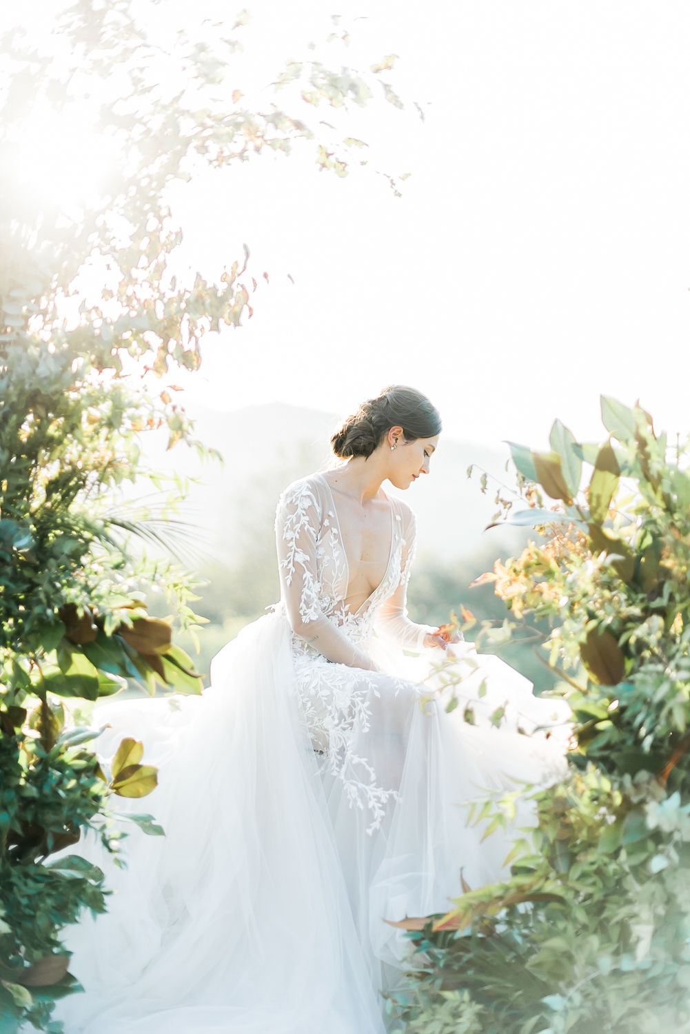fine art portrait of bride sitting on a floral arch