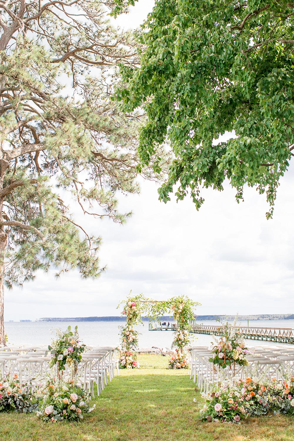 riverside wedding ceremony with garden flowers and white chairs
