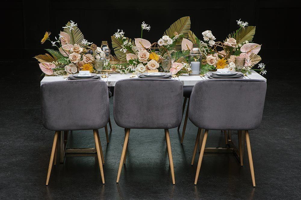 mid-century modern wedding table with velvet chairs, anthuriums and palm fronds