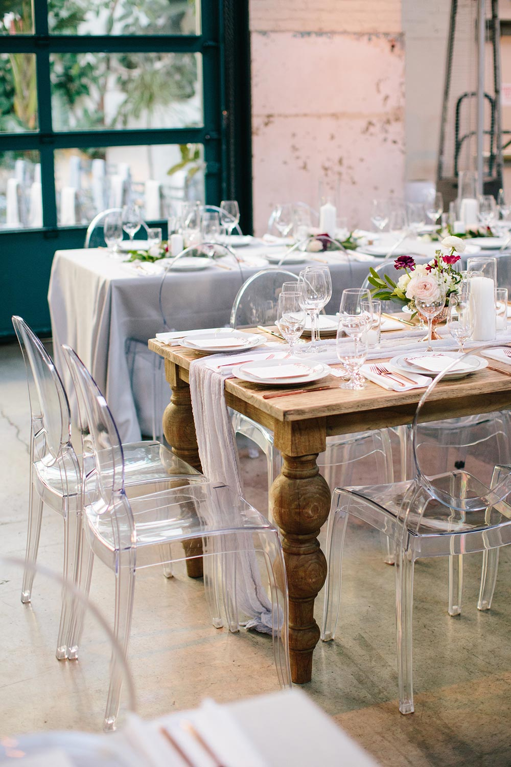 urban wedding reception with family style tables and ghost chairs