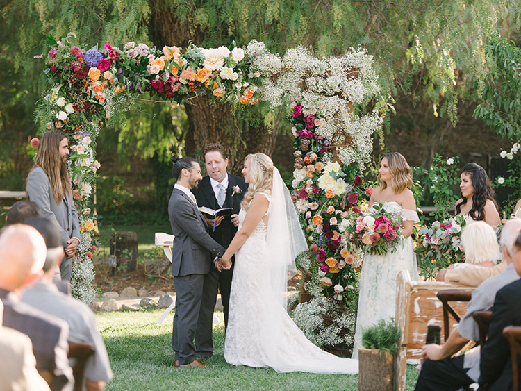 wedding ceremonies with floral arches - photo by Erica Schneider Photography https://ruffledblog.com/vegetable-garden-inspired-wedding-with-seriously-lush-details