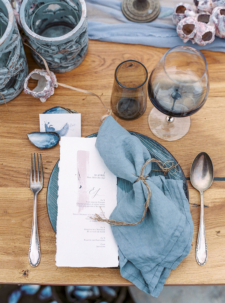 place settings with blue grey linens - photo by Wild Beach Elopement Inspiration at Cinque Terre http://ruffledblog.com/wild-beach-elopement-inspiration-in-cinque-terre