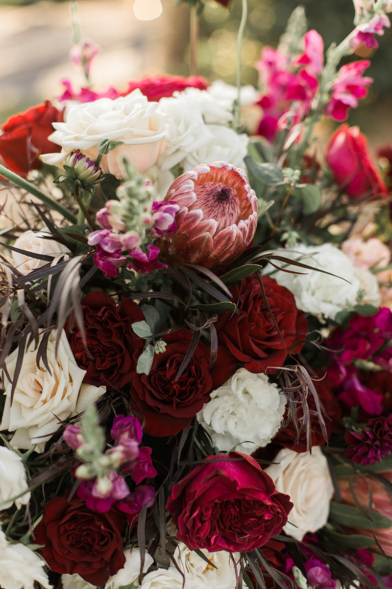 wedding flowers with fuchsia protea - https://ruffledblog.com/wine-country-wedding-inspiration-with-a-pampas-grass-arch