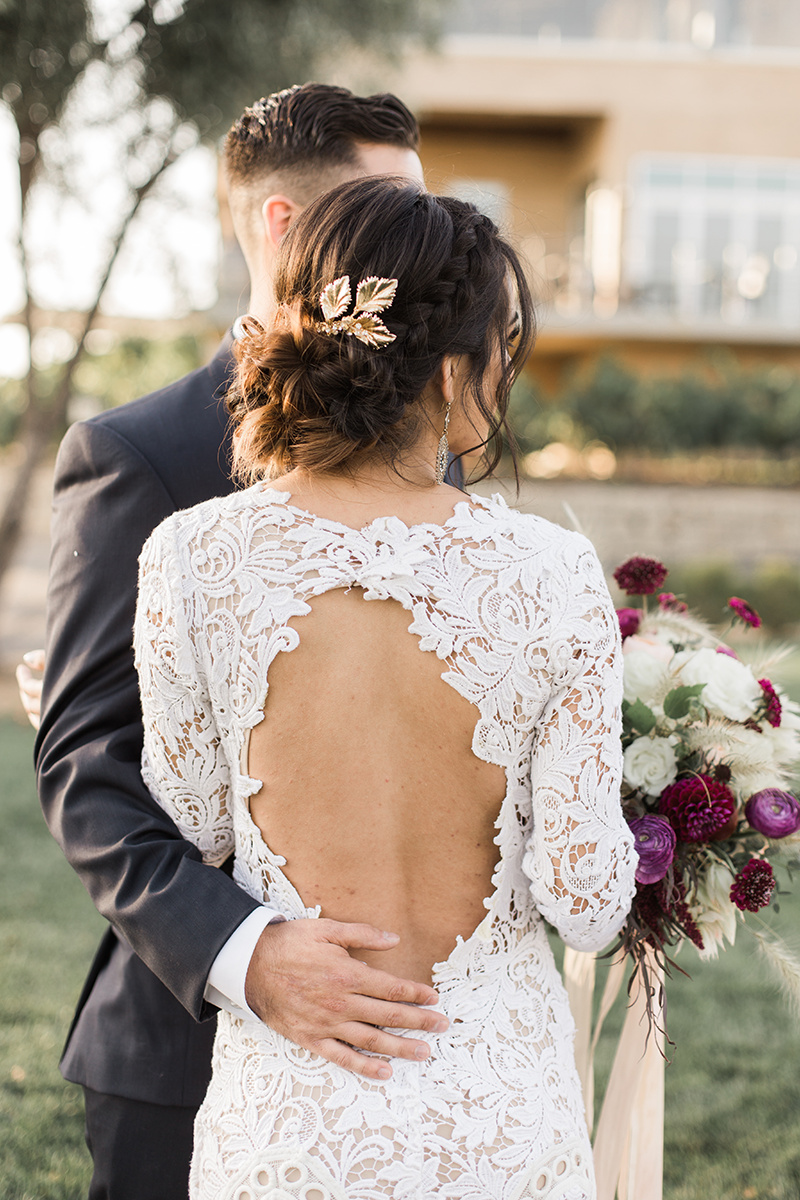 unique lace wedding dress backs - https://ruffledblog.com/wine-country-wedding-inspiration-with-a-pampas-grass-arch