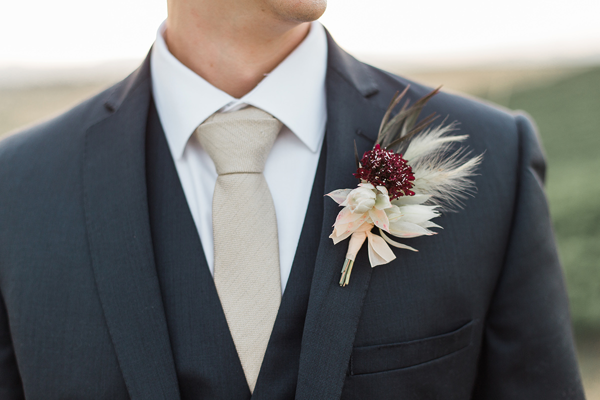 unique boutonnieres with pampas grass - https://ruffledblog.com/wine-country-wedding-inspiration-with-a-pampas-grass-arch