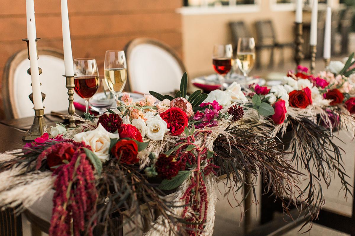 red wedding flowers - https://ruffledblog.com/wine-country-wedding-inspiration-with-a-pampas-grass-arch